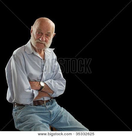 Elderly Man Crosses Arms And Looks Interested
