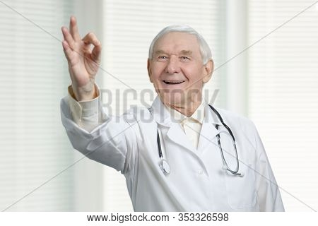 Smiling Senior Caucasian Doctor With Ok Sign. Okay Gesture From Old Physician In Jalousie Background