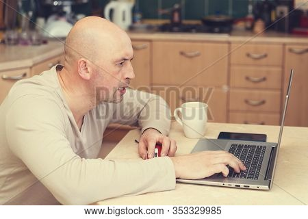 Busy Man Working At Home. Man Sitting At Home, Working On Laptop Computer. Man Working From Home Lap