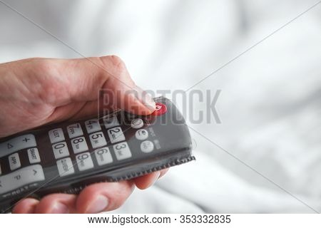 Male Hand Holds The Remote Control From The Tv On A White Background. The Man Turns Off The Tv, Clic