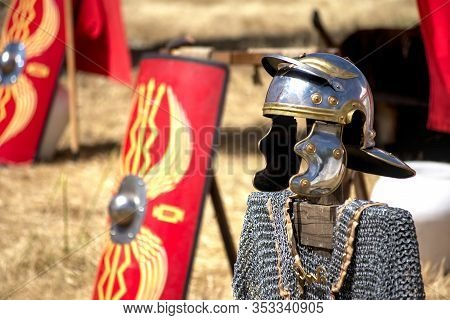 Shiny Roman Helmet With Chain Mail Placed On A Wood Strut With A Traditional Decorated Red Rectangul