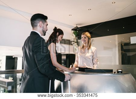 Portrait Of Two Young Business People Check-in At Hotel Reception Front Desk. Business Travel Concep