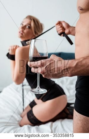 Selective Focus Of Dominant Man With Glass Of Red Wine Holding Bdsm Leash On Submissive Woman