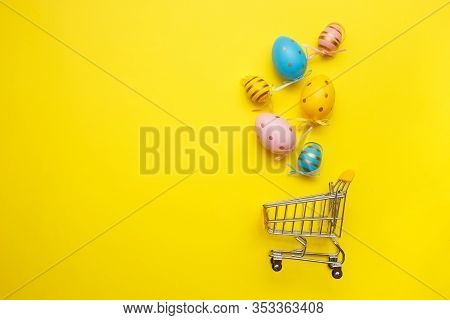 Shopping Trolley With Easter Eggs And Copy Space On Yellow Background. Easter Shopping And Sale Conc