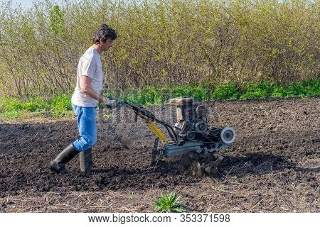 Man In Wellingtons With Cultivator Ploughing Ground In Sunny Day. Farmer Plowing Kitchen-garden In S