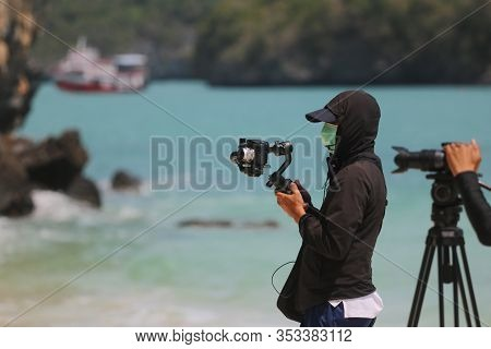 The Video Photographer Or Journalist Wearing A Mask And Recording The Tourist Activities On The Beac