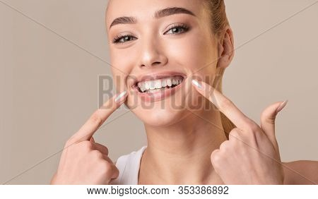Perfect Smile. Young Woman With White Teeth Touching Mouth Smiling To Camera Posing On Beige Backgro