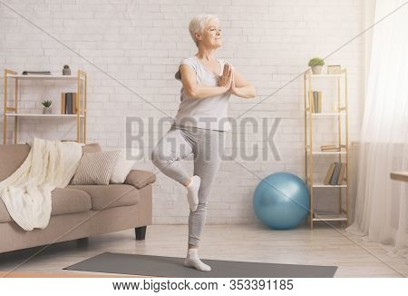 Balance In Life. Senior Woman Doing Yoga Tree Pose At Home, Free Space