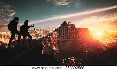Young Asian Couple Hikers Climbing Up On The Peak Of Himalaya Mountains. People Helping Each Other H