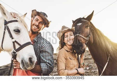 Happy Couple Having Fun With Horses Inside Stable - Young Farmers Sharing Time With Animals In Corra