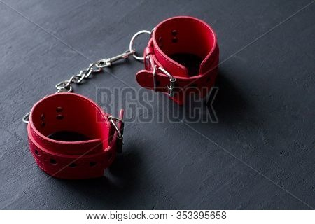 Bdsm, Bondage Play, Fetish Wear And Kinky Sex Toy Concept With Close Up, Red Leather Handcuffs On Bl