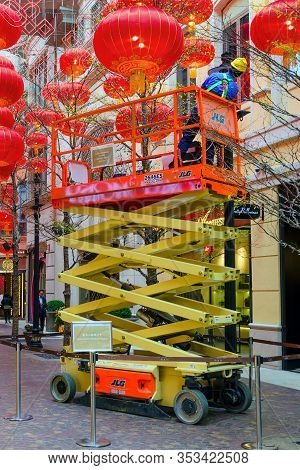 Electrician On A Hydraulic Scissor Lift Serves A Street Lamp.  Around The Decoration Of Chinese Lant