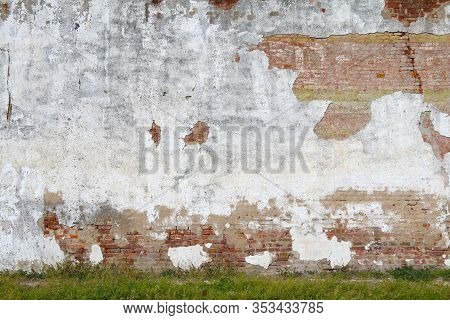 An Exposed White Stucco Concrete And Red Brick Garden Wall With Grass Verge In The Afternoon