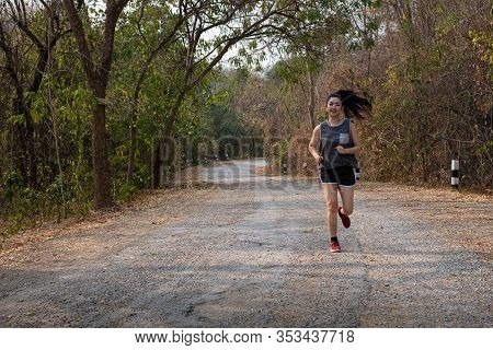 Photo Fone View Asia Young Smiling Woman Runner Running On Asphalt Old Road, Female In Sport Cloth A