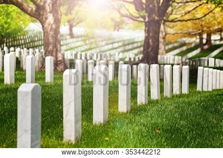 View Or Rows Of White Tombstones On The Cemetery Lit With Warm Sunlight Sun
