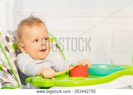 Happy Little Toddler Baby Boy Sit In Highchair Holding Plastic Spoon And Smiling