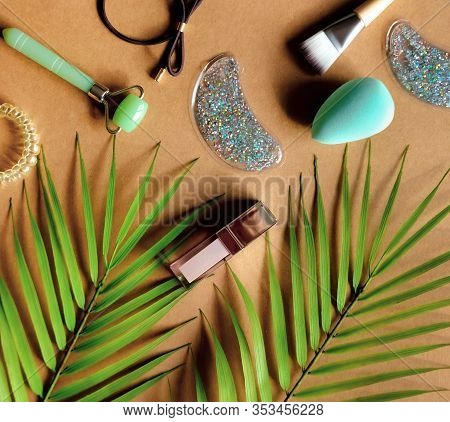 Cosmetic Products: Lip Gloss, Lipstick, Jade Roller, Brush, Patches On Natural Brown Background. Bea