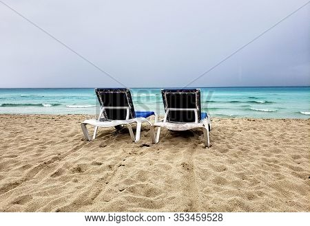 Two Loungers, Chaise-longues On A Cuban Beach Before Storm. Cloudy And Windy Weather And Sky.