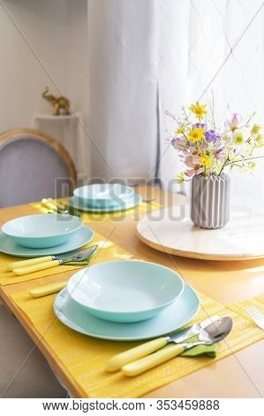 Colorful Set Of Tableware And A Bouquet Of Wild Flowers On A Brown Wooden Dining Table In Natural Li