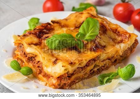 Homemade Meat Lasagna With Fresh Basil And Parmesan Cheese In A Plate On White Wooden Table. Close U