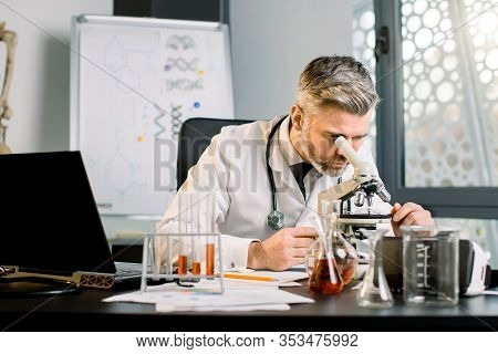 Senior Caucasian Male Scientist Working With Laptop, Test Tubes And Flasks At The Modern Laboratory.