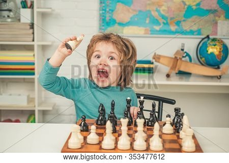 Chess School. Son Are Playing Chess And Smiling At Home. Little Clever Boy Thinking About Chess