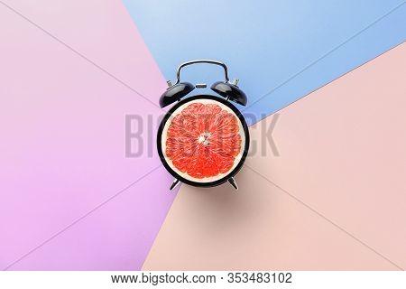 Ripe Grapefruit In Alarm Clock On Color Background