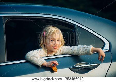 Sweet Female Child Looking Trough Car Window. Cute Pensive Girl Looking Through Window Of Car
