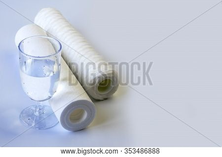 Water Filter Two Units. Near A Glass Of Clean Water. White Background, No Isolation. Close-up
