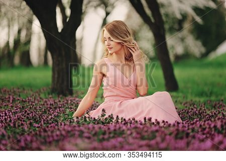 Beautiful Blonde Young Woman In Colorful Flowers. Girl With Make-up And Hairstyle In Pink Dress In B