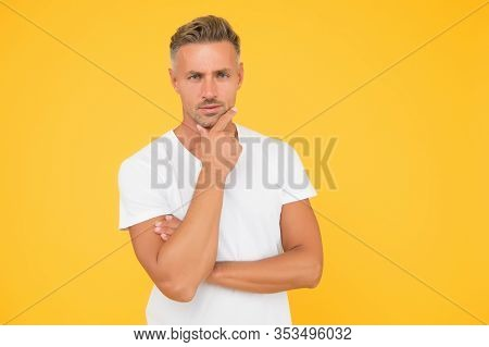 Thinking About Shaving Beard Off. Serious Guy Touch Beard Hair Yellow Background. Unshaven Man With