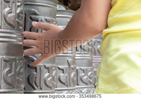 Human Hand Touching, Rotating Nepalese Traditional Metal Prayer Wheels With Mantra Om Mani Padme Hum