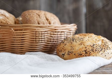 Freshly Baked Buns In A Wicker Basket And One Bun Next To It On A Wooden Background. Homebaked Bread