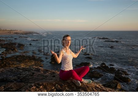 Yoga woman sitting in Lotus position on the sea beach.
