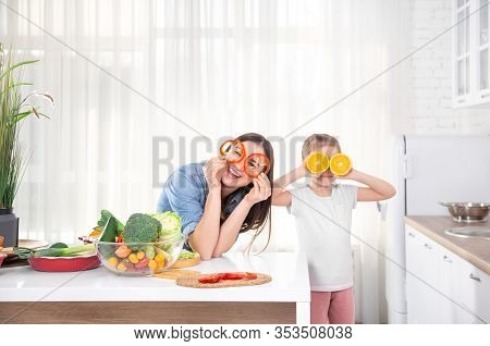 Healthy Food At Home. Happy Family In The Kitchen. Mother And Child Daughter Are Preparing The Veget
