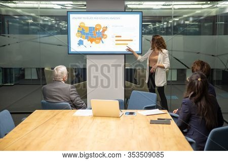 Confident Young Speaker Pointing At Screen With Percentage Chart. Experienced Analyst Explaining Det