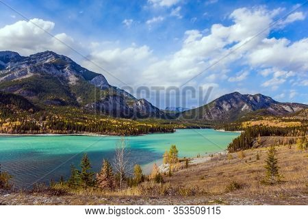 Lush multicolor autumn in the Canadian Rockies. The valley and azure icy water of the Kananaskis river. The concept of active, ecological and photo tourism