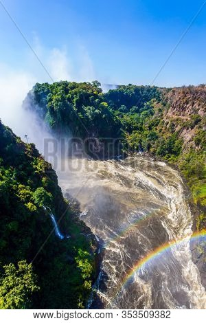 Huge rainbow in the water mist over the Victoria Falls. Victoria Park, the Zambezi River. Grand and deep Victoria Falls after the wet season. Concept of extreme and photo tourism