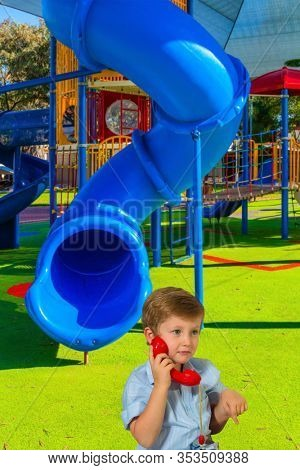Handsome blond boy with blue eyes speaks on a red telephone. Great kids playground. Attraction