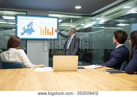 Confident Mature Speaker Pointing At Screen With Bar Chart. Experienced Analyst Explaining Details O
