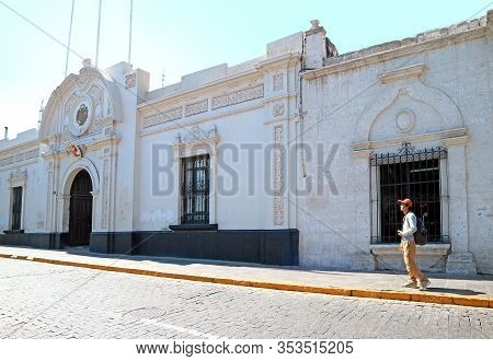Traveler Standing In Front Of White Sillar Stone Vintage Buildings Of The Old City Of Arequipa, Peru