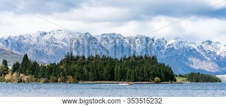 A Jet Boat Full Of Joy Riders Seeking A Thrill Along The Shores Of Lake Wakatipu Wiith A Forest And