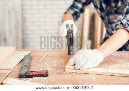 Carpenter Man Is Working Timber Woodworking In Carpentry Shop, Craftsman Is Hammering A Nail Into Ti