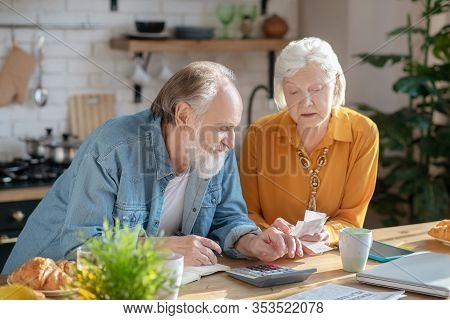 Elderly Married Couple Making Calculations Together And Looking Involved