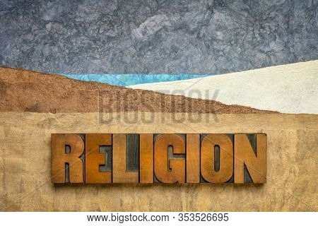 religion word in vintage letterpress wood type against abstract paper landscape, spirituality concept