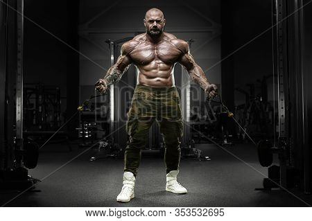 Bodybuilder Strong Athletic Man Pumping Up Muscles