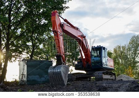 Bucked Tracked Excavator Digs Ground At A Construction Site For Installing Concrete Storm Pipes. Bac