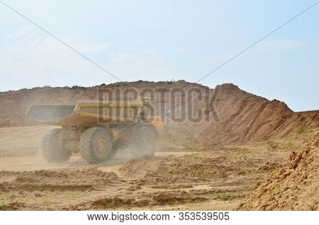Big Yellow Dump Trucks Working In The Open-pit. Transporting Sand And Minerals. Mining Quarry For Th