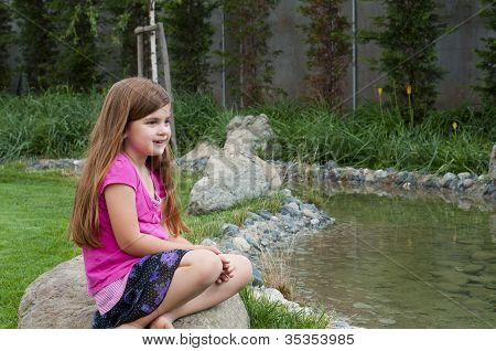 Young Girl On Rock By Calm Stream