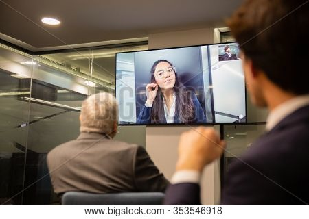 Businesspeople Having Video Conference In Boardroom. Business People Looking At Monitor Screen Durin